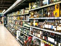 Wijnplanken met prijskaartjes op vertoning bij opslag in Kharkov, Uktaine Defocusedrijen van de flessen van de Wijnalcoholische d stock fotografie