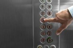 Wijsvinger die de vijfde verdieping knoop in de lift drukken stock afbeelding