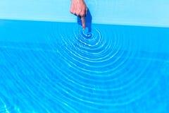 Wijsvinger die golven maken als cirkels in zwembad Stock Fotografie