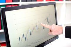Wijsvinger die het scherm met de grafiek van beursgegevens tonen Stock Fotografie
