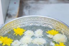 Wijwater in zilveren kom boeddhisme in tempel in geel en wit Thailand stock afbeelding