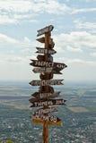 Wijzersafstanden aan verschillende steden en toerist boven op Onderstel Ma Stock Foto