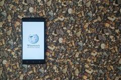 Wikipedia-Logo auf Smartphone auf Hintergrund von kleinen Steinen Lizenzfreie Stockfotos