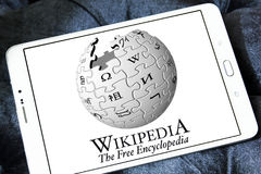 Wikipedia logo. Logo of Wikipedia on samsung tablet . Wikipedia is a free encyclopedia, written collaboratively by the people who use it. It is a special type of royalty free stock photo