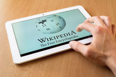 Wikipedia. Man's hand use with his fingers tablet. Wikipedia app is on the screen. Wikipedia is popular free-access online encyclopedia royalty free stock photography
