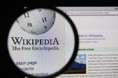 Wikipedia. Photo of Wikipedia homepage on a monitor screen through a magnifying glass stock photography