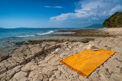 Wild Adriatic sea beach. Croatia, Losinj island. Wild Adriatic sea beach with rug for sun tanning. Croatia, Losinj island, popular touristic destination Stock Images
