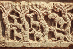 Wild animals and trees of forest on sculpured stone relief carvings from the temple. Royalty Free Stock Photography