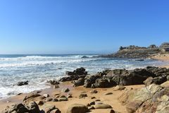 Wild beach with golden sand, furious sea, waves and prehistoric settlement ruins. Barona, Galicia, Spain. Sunny day, blue sky. stock image