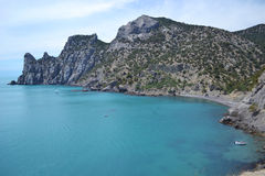 Wild beach and boat. Clean blue sea and mountains Stock Photos