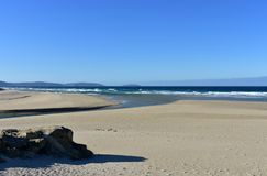 Wild beach with waves and morning light. Galicia, Spain. Galicia, La Coruña Province, Rias Altas, Spain. Beach with waves and blue sky, sunny day royalty free stock photo