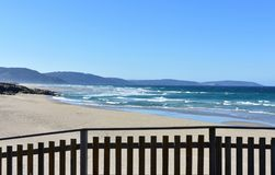 Wild beach with wooden handrail, golden sand and blue sea with waves. Sunny day, clear sky, Galicia, Coruna Province, Spain. Arteijo, La Coruna Province stock image