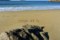"Beach with the word ""sun"" written in the sand. Rocks and blue sea with foam, sunny day. Galicia, Spain. stock photos"