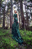 Wild beauty blonde woman long green dress in the forest Royalty Free Stock Photography