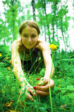 Wild berries. Pretty girl picking wild strawberries in forest Royalty Free Stock Images