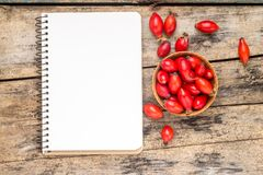 Wild berries with blank notebook on wooden table. Royalty Free Stock Photo