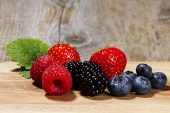 Wild berries on a chopping board Royalty Free Stock Image