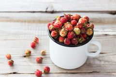 Wild berries in a cup. Wild strawberry in a cup on wooden background Stock Photo