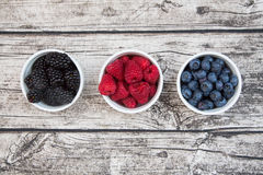Wild berries, Raspberries, blueberries and blackberries in bowls. Wood table background Stock Images
