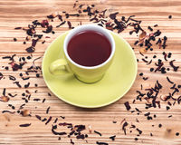 Wild berry tea in green cup with hibiscus leafs Stock Photos