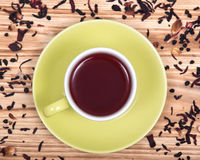 Wild berry tea in green cup with hibiscus leafs Stock Photo