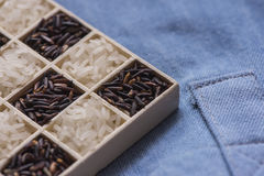 Wild black and white dry rice closeup macro shot on blue jeans. Sensitive focus Stock Photo