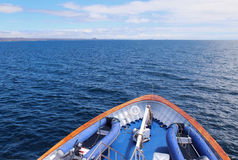 Into the wild blue yonder. View from the bow of a small cruise ship as it heads towards Santa Cruz Island in the Galapagos chain, Ecuador, over calm blue seas of Royalty Free Stock Photography
