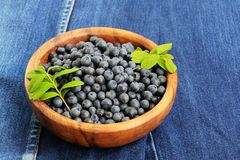 Wild blueberries with fresh green leaves in handmade wooden bowl Royalty Free Stock Photography