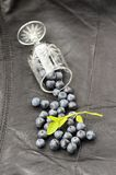 Wild blueberries scattered from small wineglass on black leather Royalty Free Stock Photos