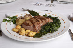 Wild boar loin barbequed. Dish on white restaurant table - Wild boar loin barbequed stock photos