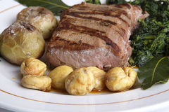 Wild boar loin barbequed. Dish on white restaurant table - Wild boar loin barbequed royalty free stock images