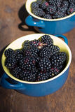 Wild, bright blackberry in blue plate - healthy fruit. Wild, bright blackberry in blue plate on brown background - healthy fruit Royalty Free Stock Image