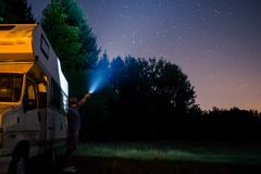 Wild camping exploring outdoors. Camping with motorhome in mountain. Man exploring outdoor with flashlight Royalty Free Stock Photos