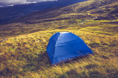 Wild camping with tent on mountain Stock Image
