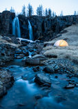 Wild Camping by a Waterfall in Iceland. My tent. set up next to a waterfall in Northern Iceland, is illuminated from inside just after sunset. A long exposure Royalty Free Stock Photo