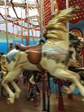 Wild Carousel Horse. Motion, color and a blurred effect makes this carousel horse seem unrestrained Stock Photo
