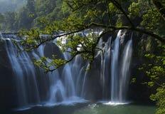 Wild cascade between stones in  forest landscape Stock Photos