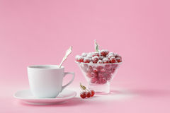 Wild cherry in a plate with a mug of coffee on a pink Royalty Free Stock Photo