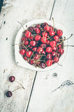 Wild cherry sweet merry. Red ripe juicy cherry in metal plate on white rustic wooden background. Sweet summer berries. Freshly harvested merry. Directly above Stock Images