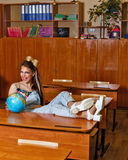 Wild Child in geography class with globe. Stock Photo