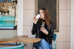 Wild city life consumes lots of energy. Attractive thoughtful and stylish female tourist, sitting cafe patio and. Drinking coffee, looking aside, thinking about Stock Photo