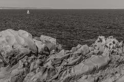 Wild coastline, Testa Cape, Sardinia. Black and white picture of wild rocky coastline with boat in the distance Stock Photo