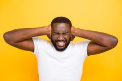 Wild depressed shocked toothy manly mulato guy in white t-shirt,. Closing ears with palms, isolated over bright vivid yellow background stock photos