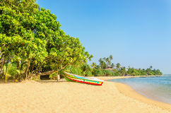 Wild and exotic Asian beach with colorful boat Stock Images