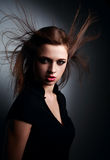 Wild expressive young woman with wind hairstyle and vamp look on. Dark background Royalty Free Stock Photos