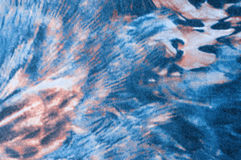 Wild feather texture. Feather pattern close up on polyester textile, blue brown and white Stock Image
