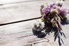 Wild field flowers gathered in a small bunch and on a wooden tab Stock Photo
