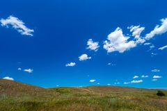 Hilly area with a beautiful blue sky. Wild field and sky with white light clouds Stock Images