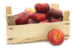 Wild flat nectarines in a wooden crate Royalty Free Stock Images