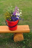 Wild flowers bouquet on yellow wooden bench in red bucket Stock Photo